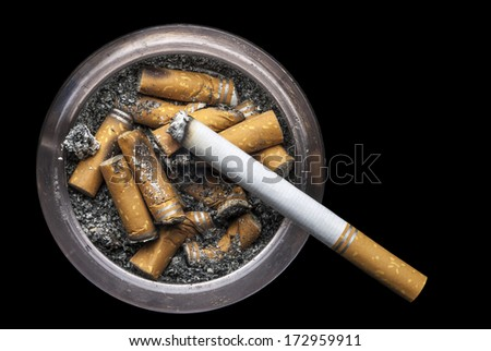 Grungy Ashtray with ash and cigarette butts and one lit cigarette on a black background. - stock photo