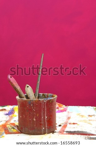 Grungy background : Artist studio working place with used paintbrushes in front of purple color with copy space for image or text - stock photo