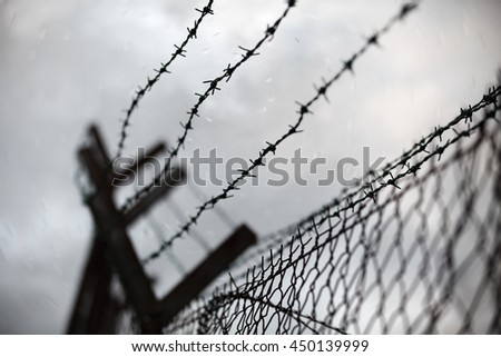 Grungy barbed wire fencing for an apocalyptic backdrop.  - stock photo