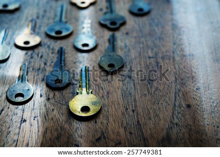 Grungy brass keys aligned in on a old wooden desk. Security and encryption concept image. Shallow depth of field. Focus is on forehand gold key. Intentionally shot in surreal color.   - stock photo