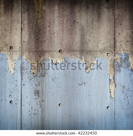 Grungy concrete wall with peeling blue paint