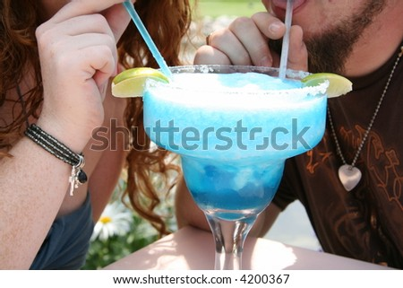 Grungy Couple Sharing a Fruity Concoction - stock photo