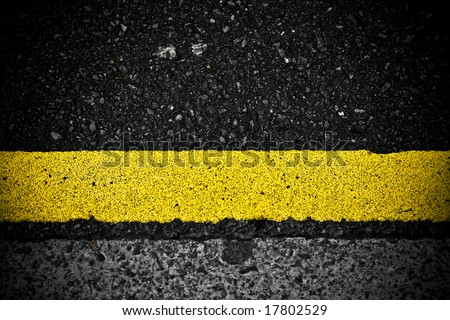 grungy, dirty view of asphalt with distinct yellow stripe - stock photo