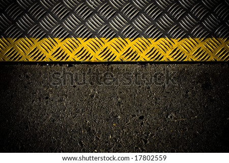 grungy, dirty view of asphalt with distinct yellow stripe on metal surface - stock photo