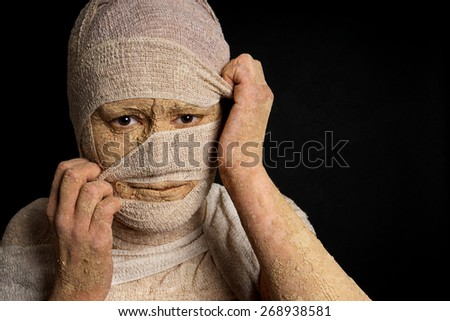 grungy female egyptian mummy pulling at bandages halloween concept - stock photo