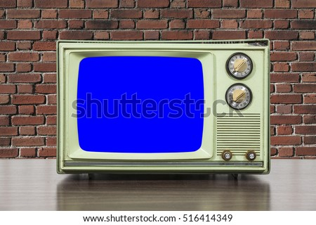 Grungy green vintage television set with brick wall and chroma key blue screen.
