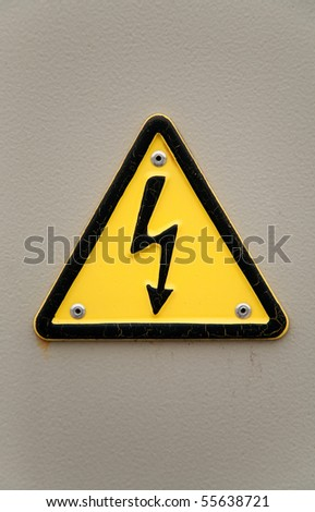 Grungy high voltage sign over gray wall background - stock photo