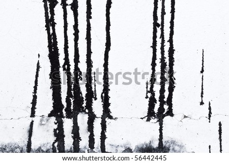 Grungy leaking black paint on white wall - stock photo