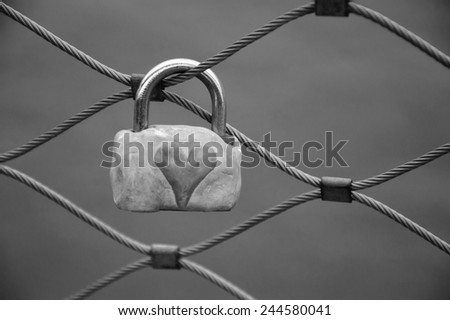 Grungy love padlock with heart decoration attached to the bridge in Paris. Valentine's day background. Aged photo. Black and white. - stock photo
