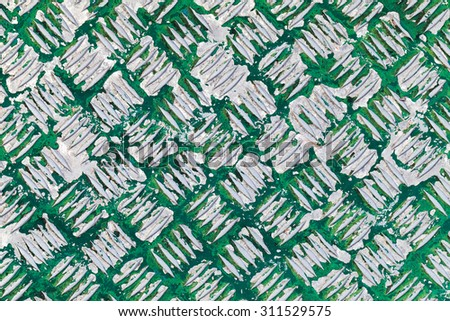 Grungy metal surface with diamond plate pattern under old green paint layer - stock photo