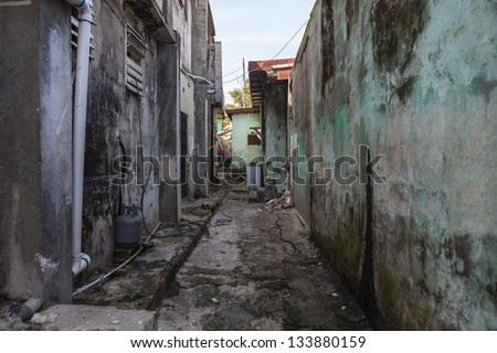 Grungy narrow dangerous looking barrio back alley. - stock photo