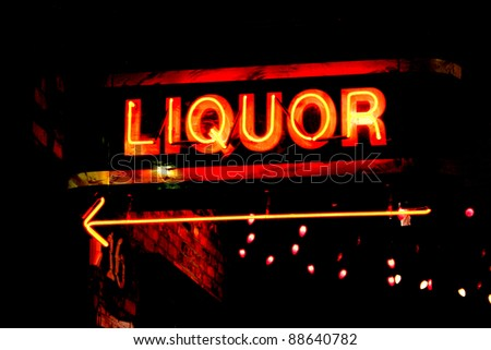 grungy neon sign pointing the way to a bar - stock photo