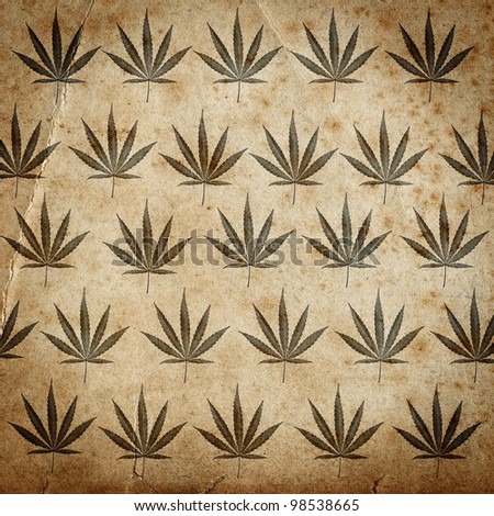 Grungy old paper background with cannabis leaves - stock photo