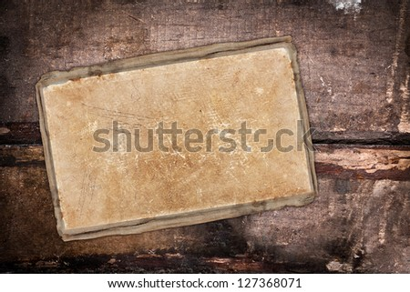 Grungy old paper sheet on a dark wooden background