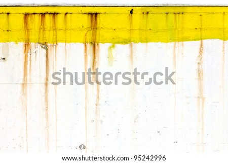 Grungy old wall with peeling yellow paint and dripping rusty lines creates unique background texture. - stock photo