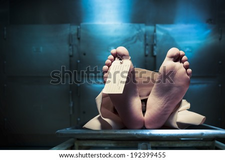 Grungy photo of feet with toe tag on a morgue table - stock photo