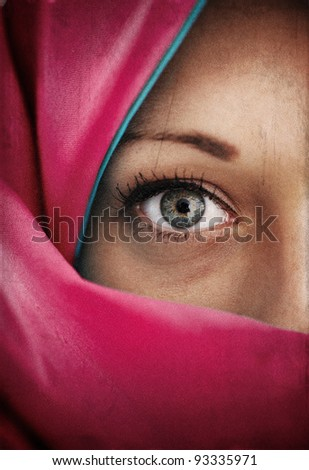 Grungy photo of Muslim woman with green eyes (grain added) - stock photo