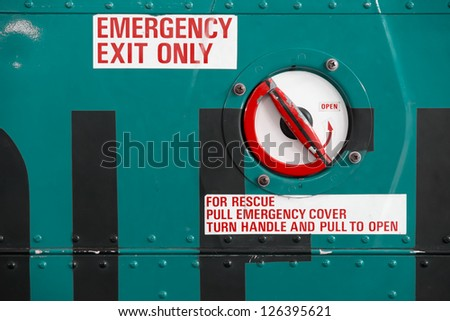 grungy red emergency exit text on helicopter - stock photo
