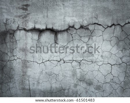 Grungy stone wall with many cracks. - stock photo