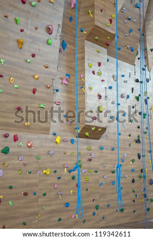 Grungy surface of an artificial rock climbing wall with toe and hand hold studs. - stock photo