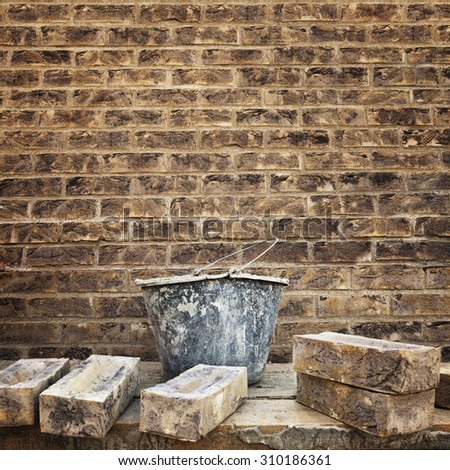 Grungy textured brown brick wall. Bucket with masonry cement and several bricks at foreground. Space for text. - stock photo