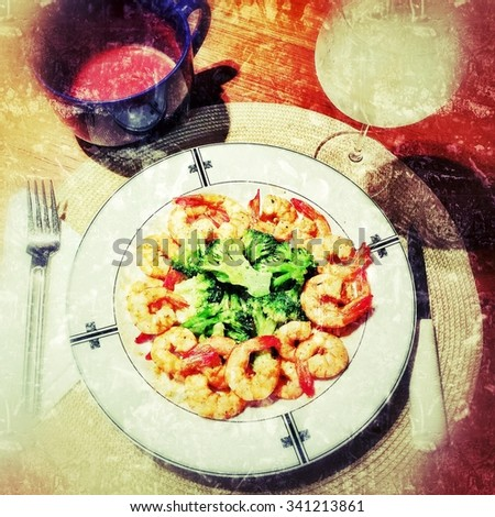 Grungy, textured, colorful broccoli and shrimp dinner with homemade cocktail sauce and a Frozen slushy girly drink in a brandy snifter