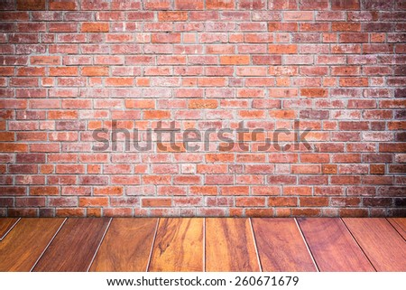 Grungy textured red brick and stone wall with warm brown wooden floor inside old neglected and deserted interior, masonry and carpentry brickwork concept - stock photo