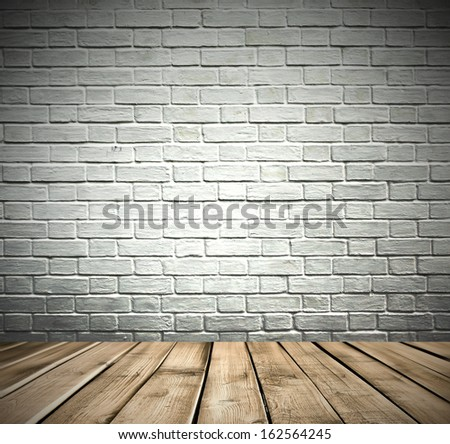 Grungy textured white and gray brick darken room and stone wall with warm brown wooden floor inside old neglected and deserted interior, masonry and carpentry brickwork concept - stock photo