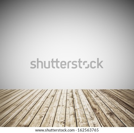 Grungy textured white brick and stone wall with warm brown wooden floor inside old neglected and deserted interior, masonry and carpentry brickwork concept - stock photo