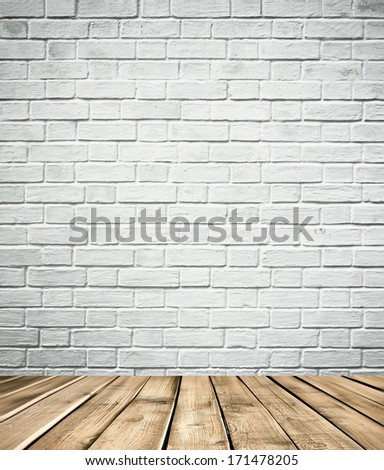 Grungy textured white brick and stone wall with warm brown wooden floor inside old neglected and deserted interior, masonry and carpentry brickwork concept
