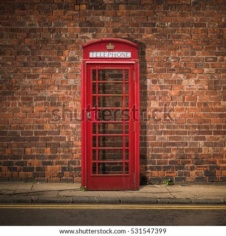 Grungy Traditional Red British Telephone Box Against A Red Brick Wall
