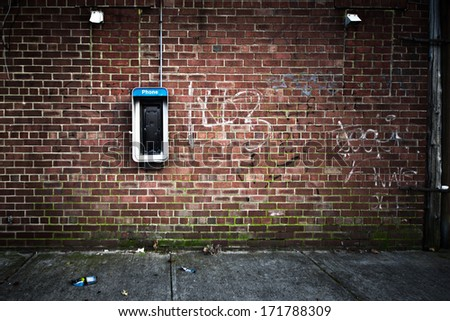 Grungy urban background of a brick wall with an old out of service payphone on it - stock photo