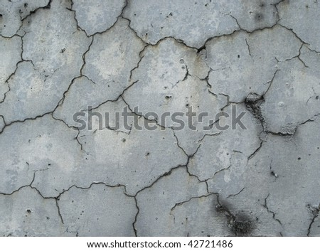 Grungy urban wall with multiple cracks