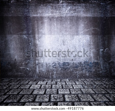 Grungy wall and cobble stone floor. - stock photo