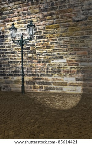 grungy wall and streetlamp at night shedding spotlight - stock photo
