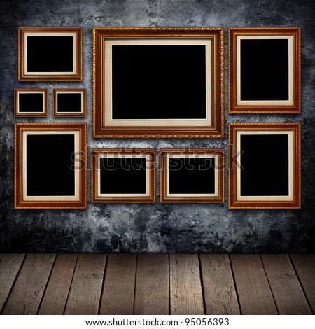 Grungy wall with gold frames and old wood background. - stock photo