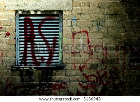 grungy wall with graffiti tag at night - stock photo
