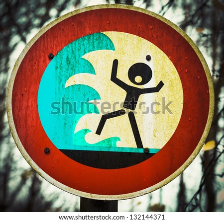 Grungy warning sign for flash flood  flooding  big tidal waves or tsunami with a pictorial signboard showing a person shouting out in panic about to be engulfed by high water - stock photo