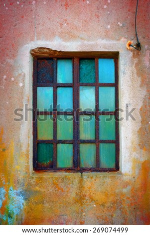 Grungy window with rusty iron bars and green old glass - stock photo