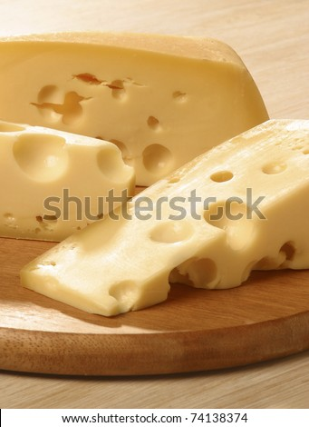 Gruyere cheese is sweet but slightly salty, with a flavor that varies widely with age. It is often described as creamy and nutty when young, becoming with age more assertive, earthy, and complex. - stock photo