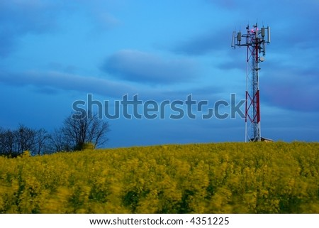 GSM transmitter station in the evening on a field - stock photo