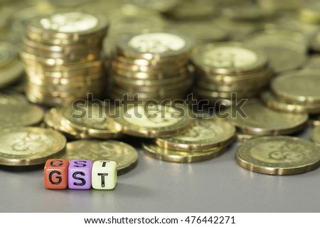 GST or Good and Services Tax word written on colorful dice and gold coins in the background