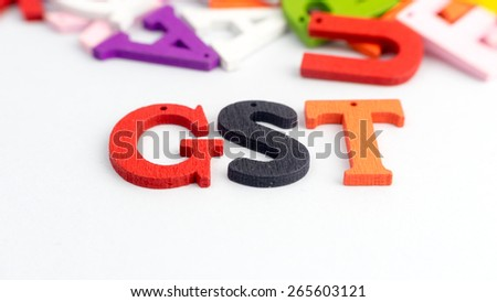 GST word with mix of colorful wooden alphabetical letters. Slightly defocused and close-up shot. Copy space. - stock photo