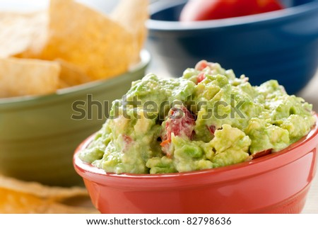 Guacamole - A studio shot of homemade guacamole in a red bowl, tortilla chips in a green bowl and a tomato in a blue bowl. - stock photo