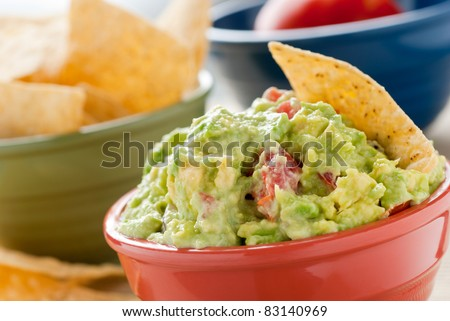 Guacamole and Chips - A studio shot of homemade guacamole in a red bowl., tortilla chips in a green bowl and a tomato in a blue bowl. - stock photo
