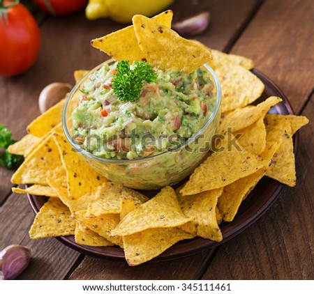 Guacamole avocado, lime, tomato, onion and cilantro, served with nachos - Traditional Mexican snack - stock photo