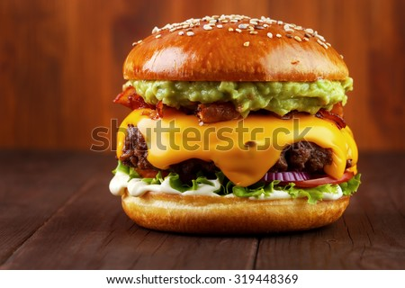 Guacamole beef burger with melted cheese and bacon on wooden background - stock photo
