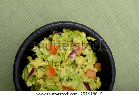 Guacamole in a bowl on green background
