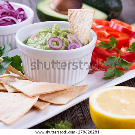 Guacamole in porcelain Bowl with mexican Tortilla Chips nachos and Ingredients - stock photo