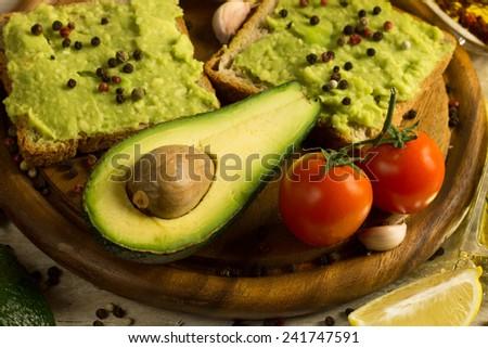 Guacamole sandwich with fresh avocado fruit on a cutting board - stock photo